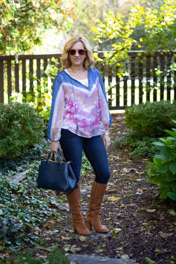 Pairing a tie-dyed sheer peasant blouse with jeans and suede kneed boots.
