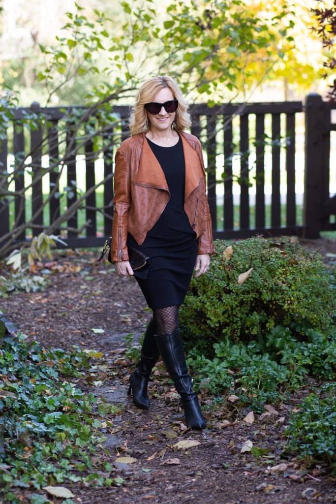 Mixing a dark tan leather jacket with a black dress and knee boots.