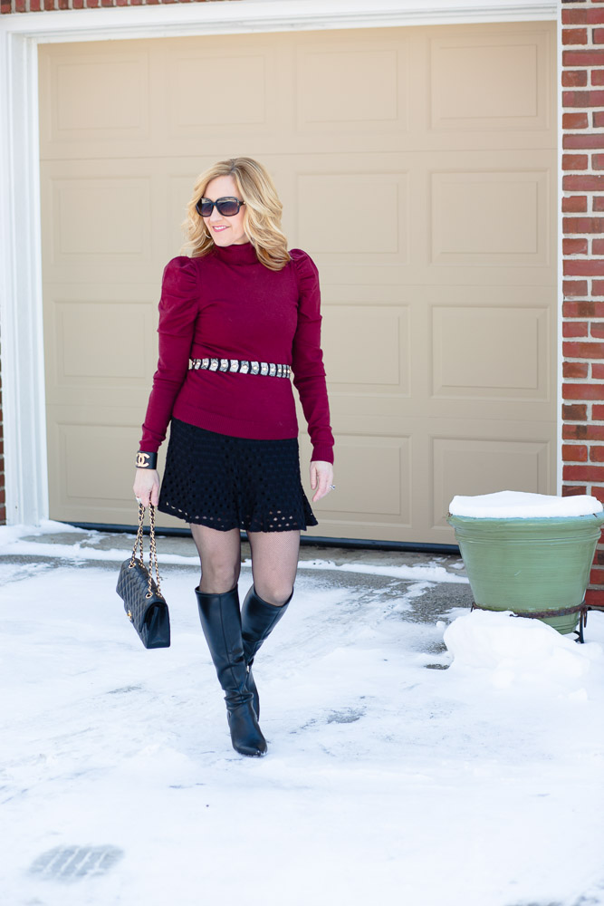 Styling a burgundy puff sleeve turtleneck over a little black dress and adding black knee boots.