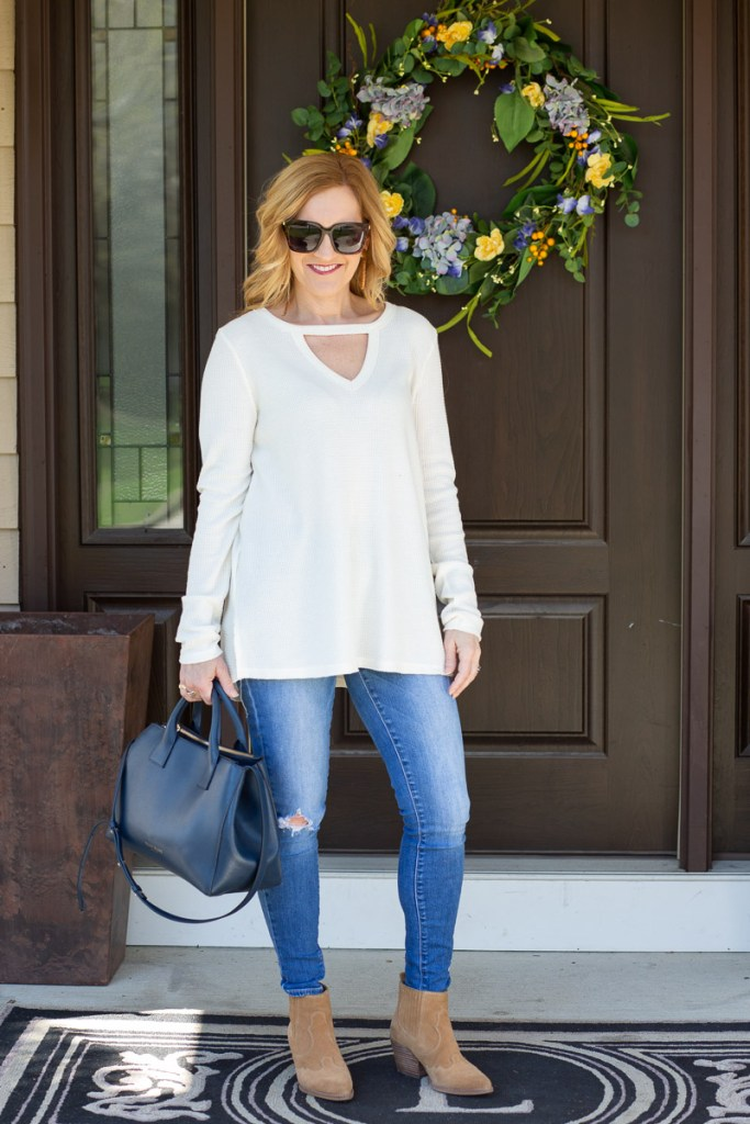 A white tunic paired with skinny jeans and suede booties.
