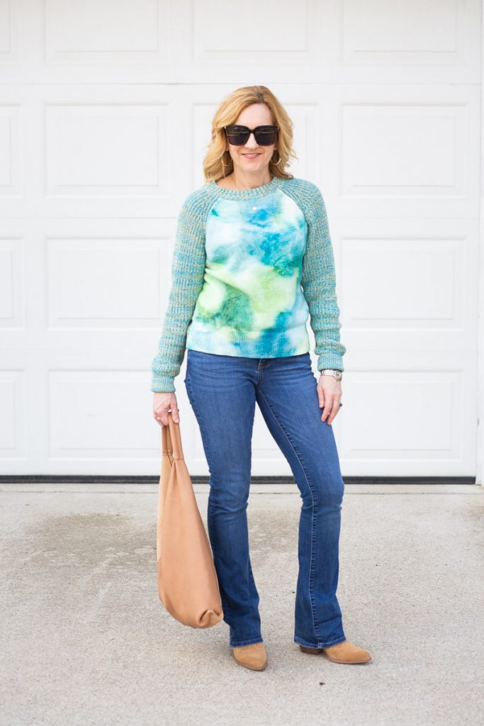A tie-dyed sweater paired with bootcut jeans and suede booties.