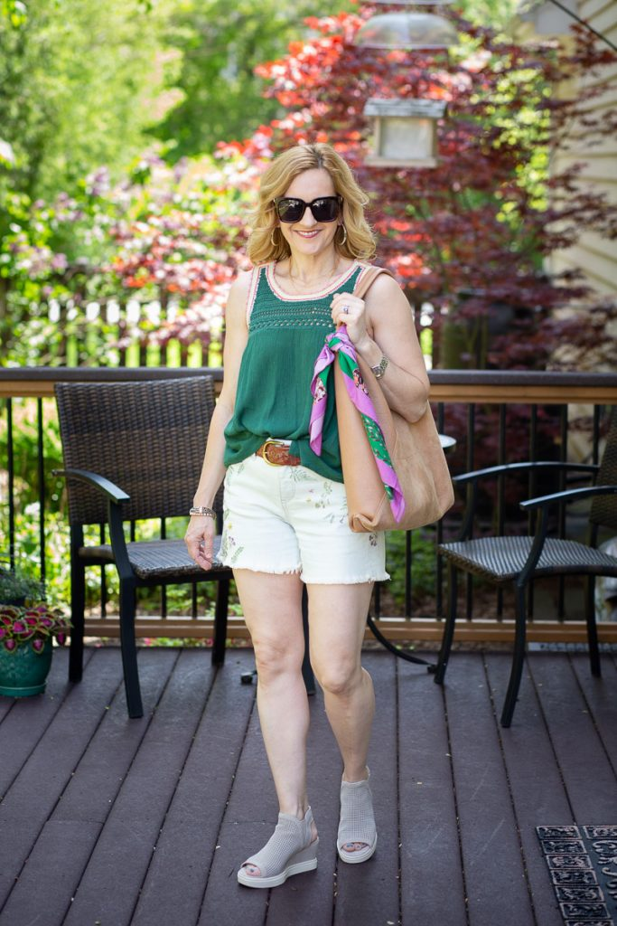 Pairing embroidered denim shorts with a green tank and wedges.