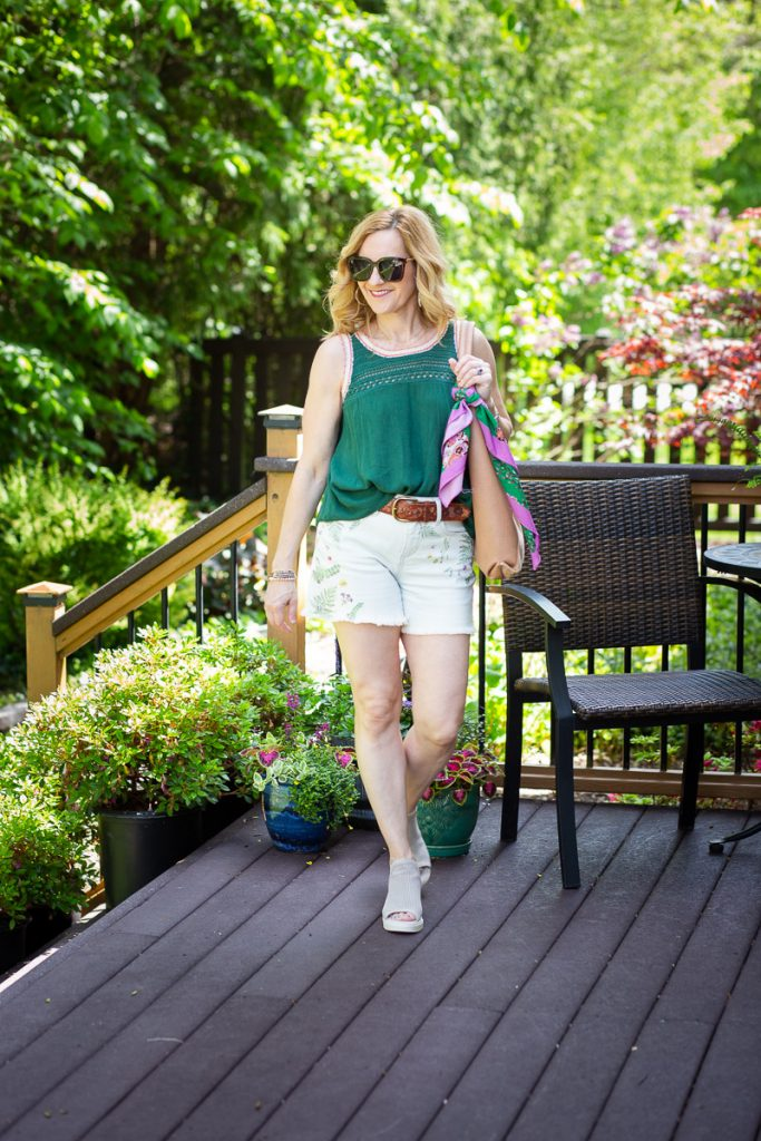 A casual summer look featuring a green tank and denim shorts.