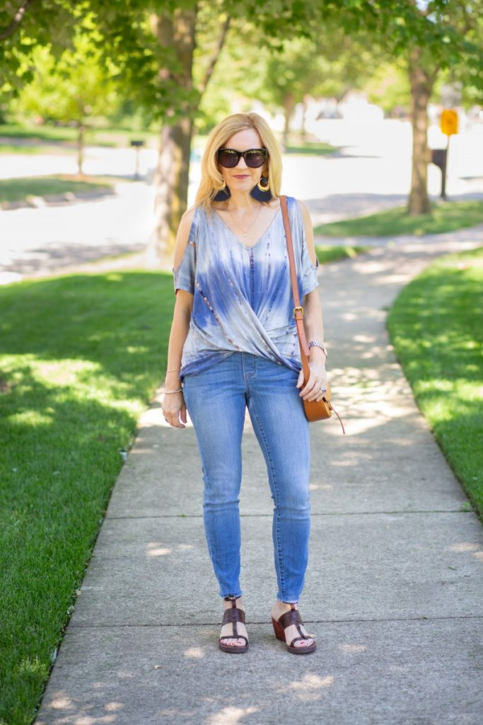 Styling a cut out tie dyed cold shoulder top with skinny jeans and sandals.