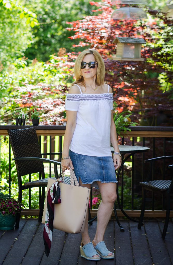 Wearing a white cold shoulder top with a denim pencil skirt.
