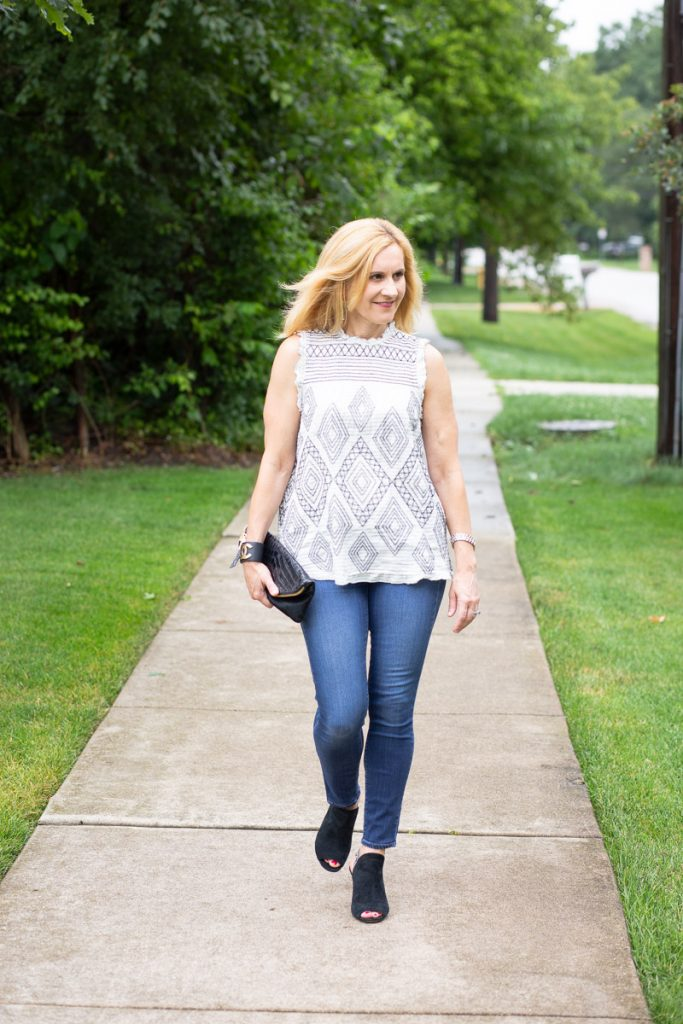 A white embroidered blouse paired with dark skinny jeans and slingback sandals.