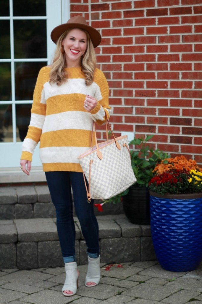 A chic fall look featuring a striped tunic sweater and skinny jeans styled by Laura Bambrick.