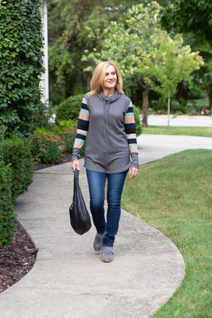 Styling a cozy striped tunic top with dark jeans and grey booties.