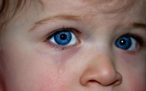 Close-up of a child's blue eyes with a tear streaming down.