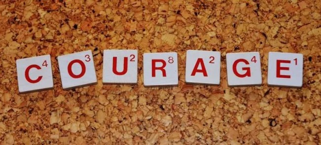 The word courage spelled in Scrabble tiles on a cork background.