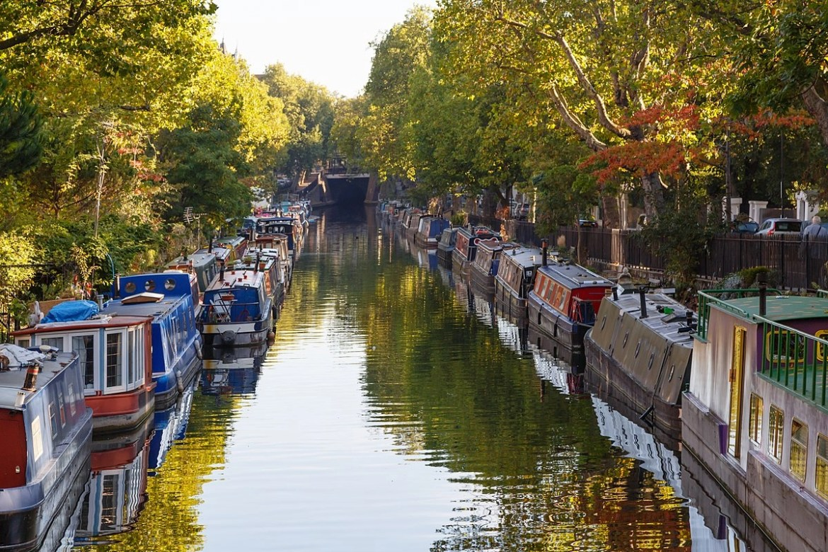 Narrow canal similar to Venetian canals with vivid boats on each side, London