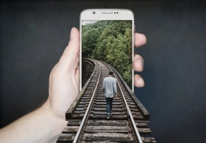 An unrealistic photo with a hand holding a phone and a man walking somewhere along the railroad.