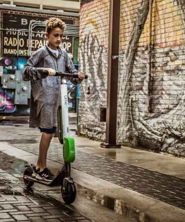 boy standing on black and white kick scooter