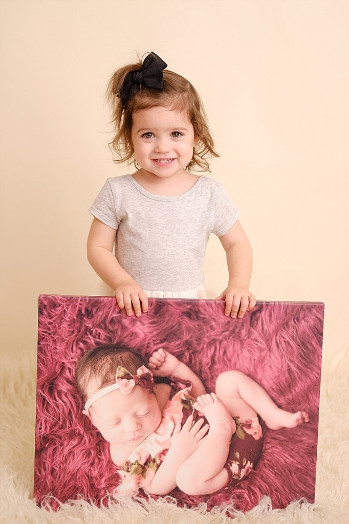girl posing with her newborn photo