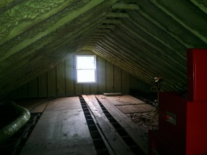 Mostly empty attic. The green in the ceiling is spray foam insulation and you can see old duct work and the loose boards that served as a floor.