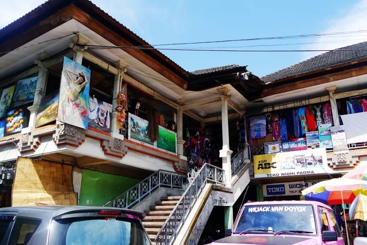 Image of paintings hanging outside building in Ubud market