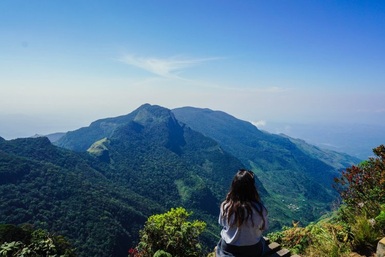 Image of girl sitting on platform at edge of cliff at World's End in Sri Lanka
