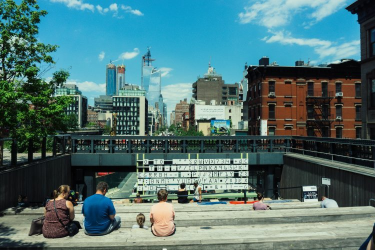 Image of people hanging out on the high line in New York's meatpacking district with the skyline in the background