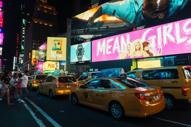 Image of yellow taxis and billboards lit up at night in Times Square New York