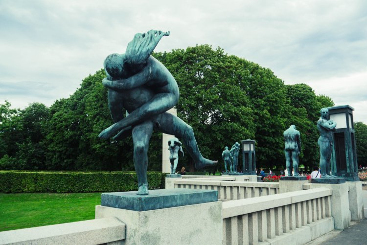 Image of copper sculpture of man and woman hugging on bridge in Vigeland  Sculpture Park Oslo