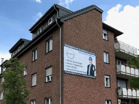 Haus mit Gaube und Balkonen und einem Plakat auf einer Klinkerwand