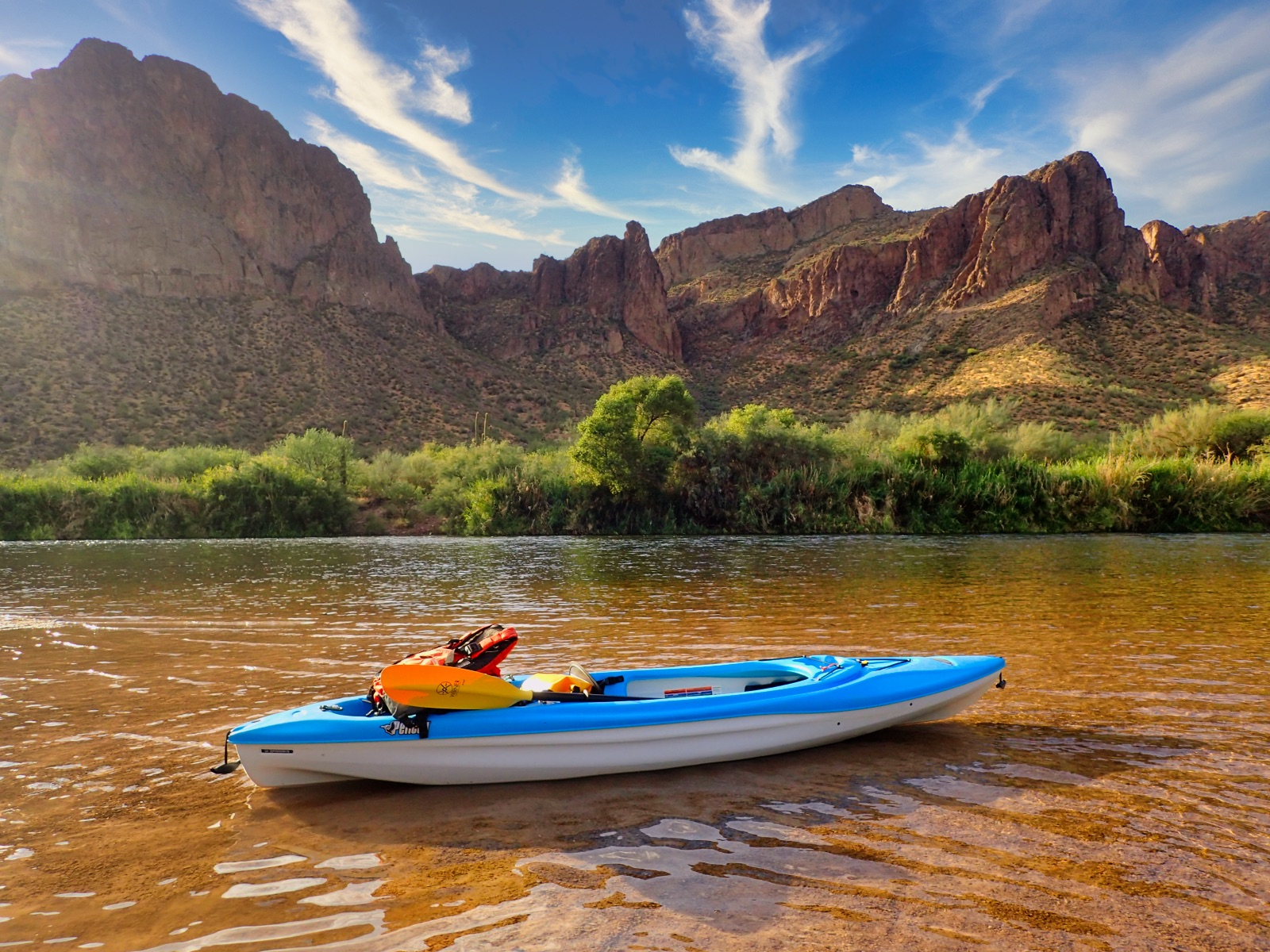 Blue kayak in shallow water with cliffs in background