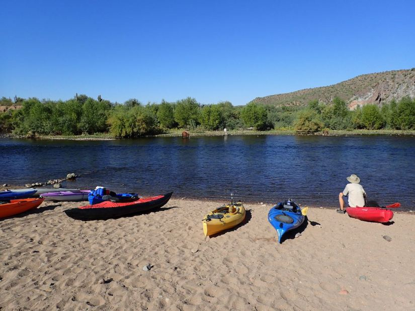 kayaks on beach with river in background