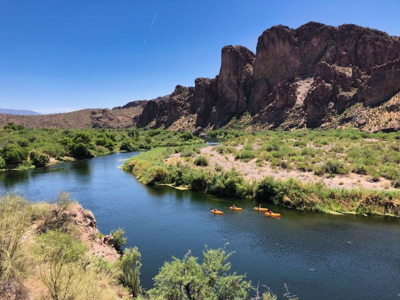 Four kayakers paddle down the river with cliffs behind them