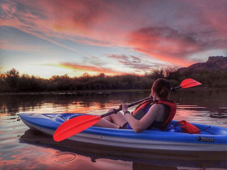 Woman paddling during colorful sunset
