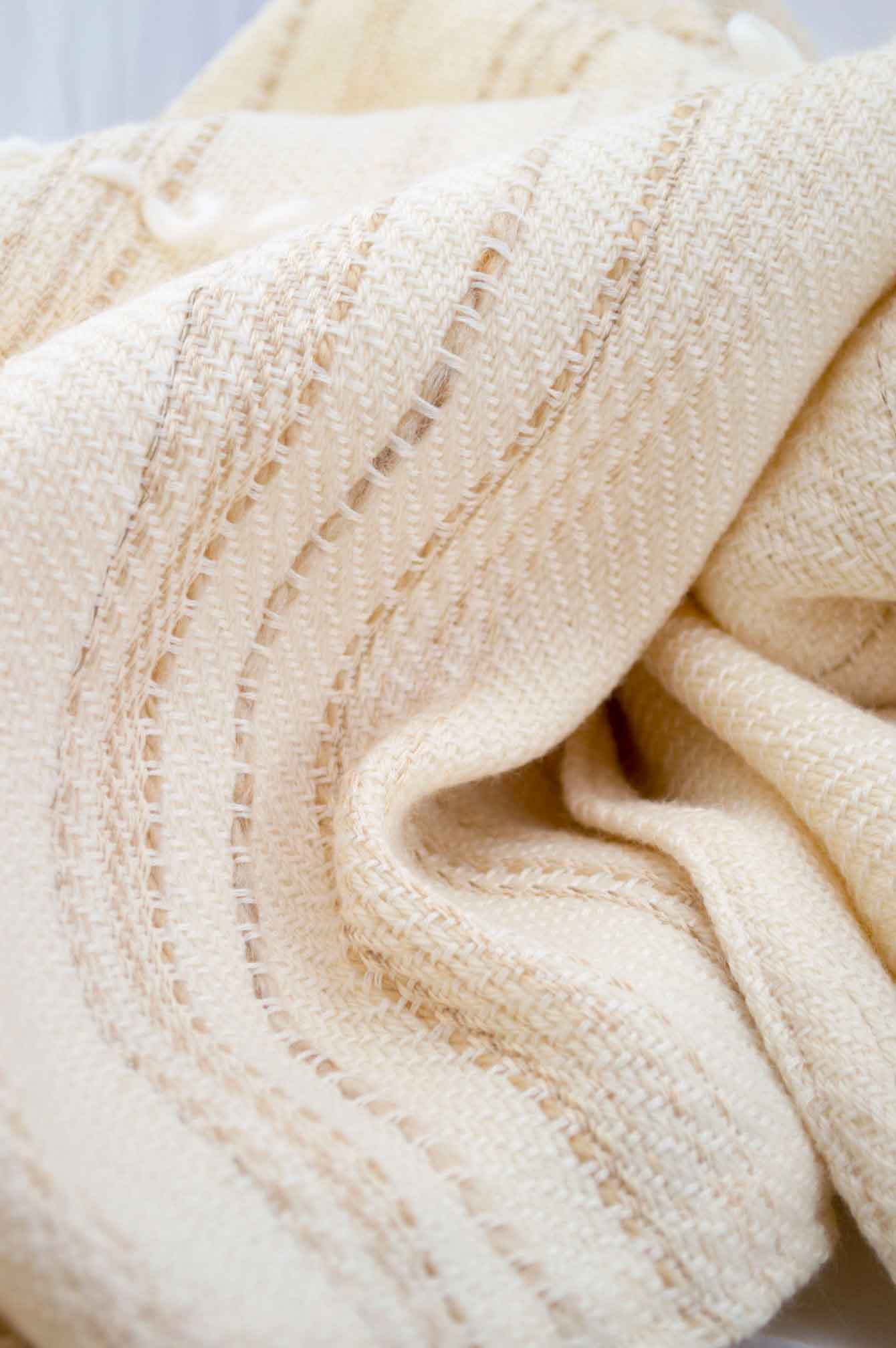 Throw blanket created with white cashmere, ecru wool plus some linen and beige cotton threads slipped into the throw blanket. White wool loop lines added after weaving the piece.  Technique: Throw blanket hand-woven in a traditional way on non-mechanical looms in the 7th arrondissement of Paris in France.  Finishing: Right edge. Double stitching. 4 pompoms 9 cm high. Two tones, beige silk and white cashmere.  Size: 140 x 170 cm.  Single piece / 1 copy only.