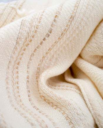 Throw blanketcreated with white cashmere, ecru wool plus some linen and beige cotton threads slipped into the throw blanket. White wool loop lines added after weaving the piece.  Technique:Throw blanket hand-woven in a traditional way on non-mechanical looms in the 7th arrondissement of Paris in France.  Finishing: Right edge. Double stitching. 4 pompoms9 cm high. Two tones, beige silk and white cashmere.  Size: 140 x 170 cm.  Single piece / 1 copy only.