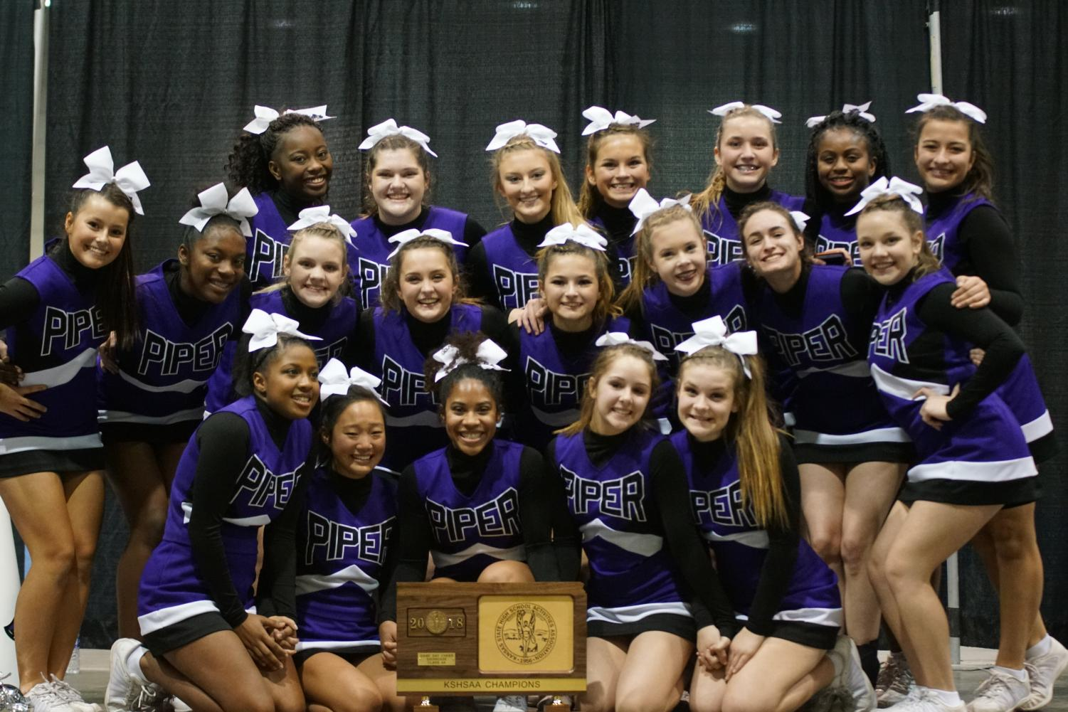 Cheer team celebrates State Game Day Competition win with trophy.