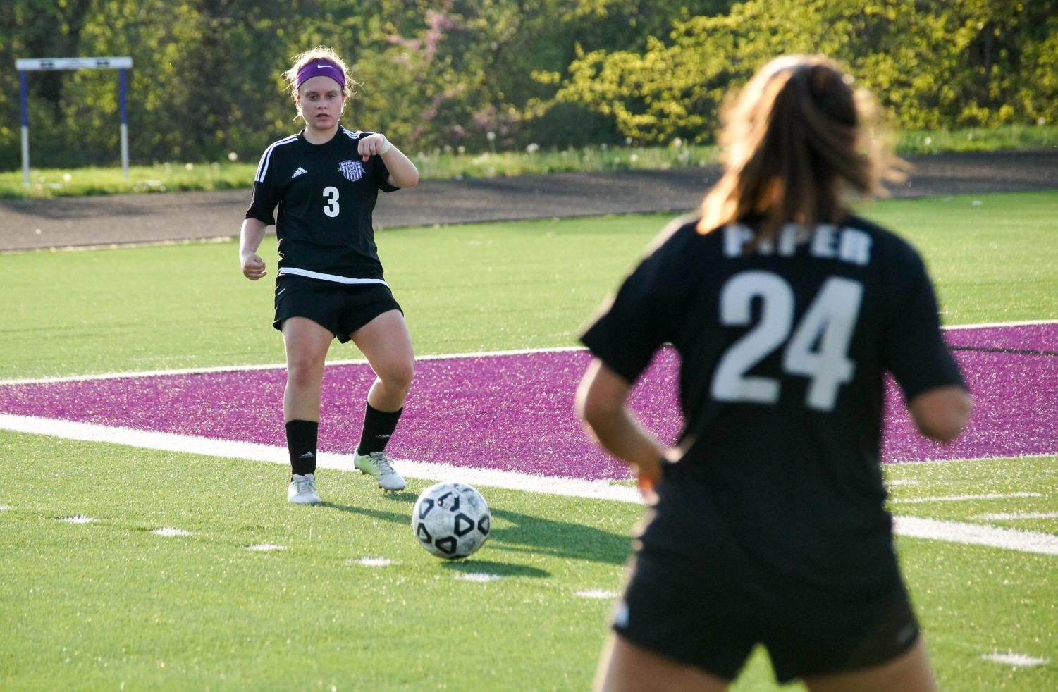 Junior Emily Brandt passes the ball to a senior teammate Josie Barbosa during a game against Bishop Miege.
