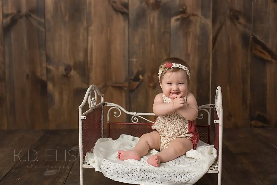 Smiling baby girl sitting on metal bed by Colorado Springs baby photographer K.D. Elise Photography.