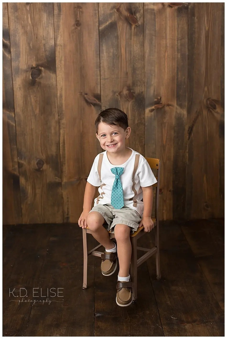 Smiling boy with a tie shirt sitting on a wooden chair.