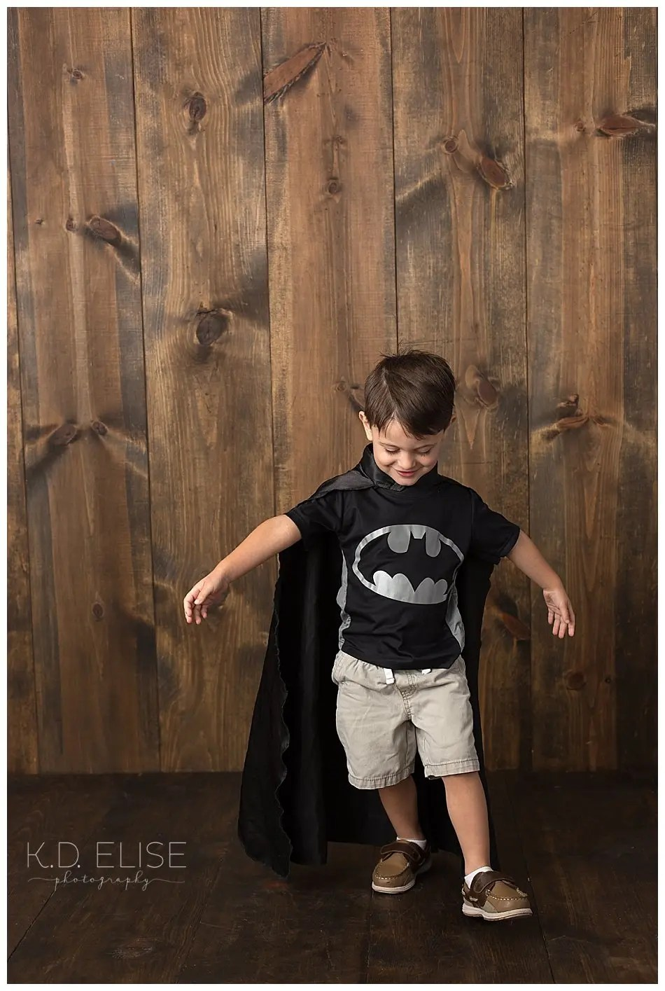 Little boy in batman shirt and cape during his third birthday portraits.