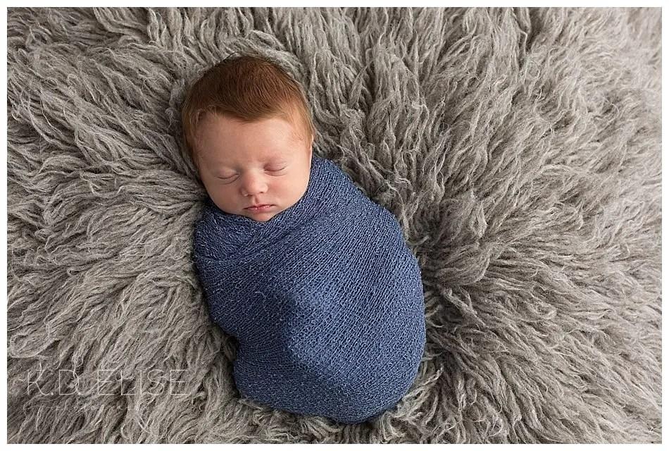 Newborn baby boy wrapped in blue laying on a grey fur.