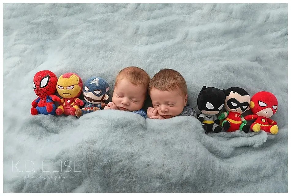 Newborn twin boys laying curled up next to superhero stuffed animals.
