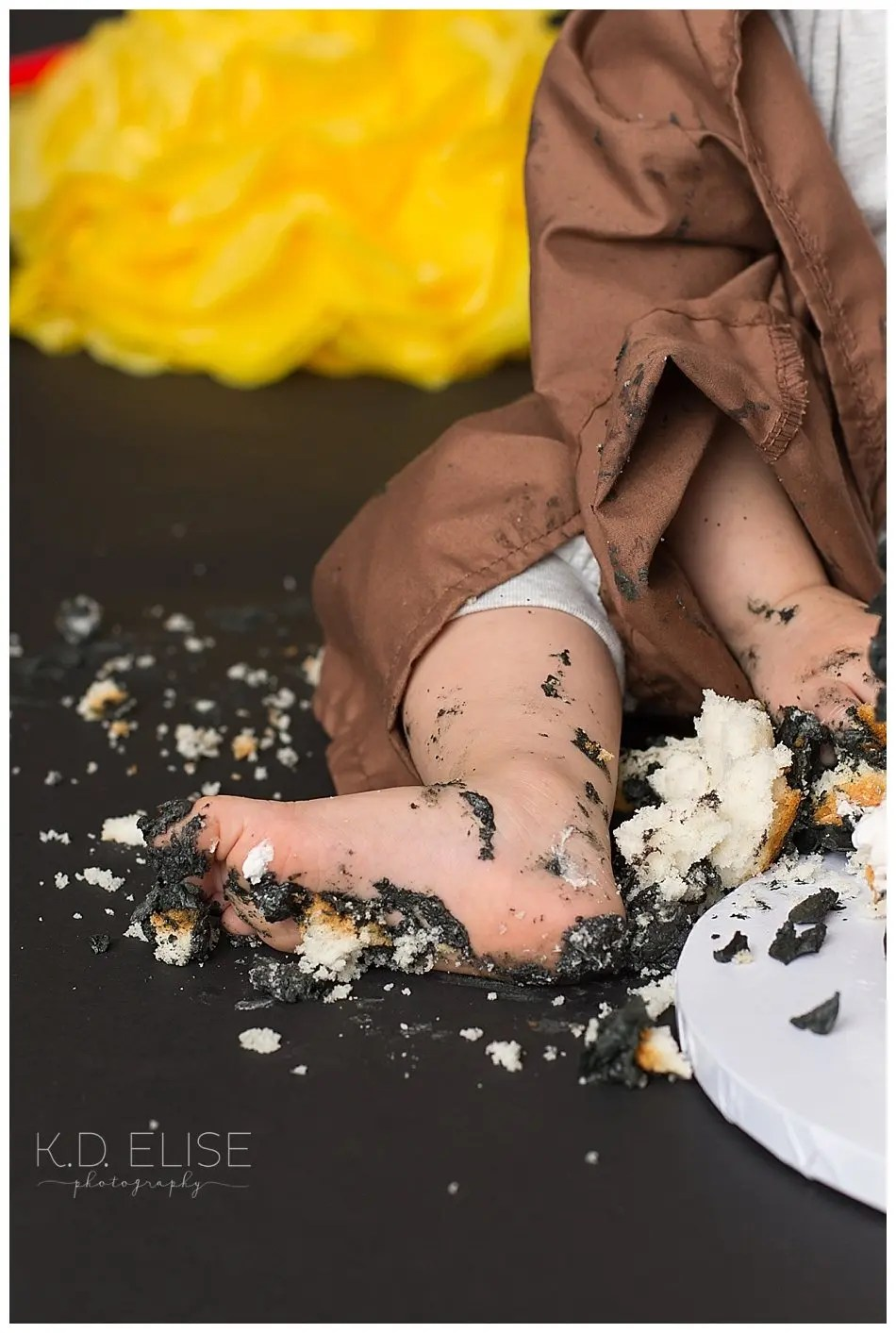 Close up photo of baby boy's cake covered feet during baby's first birthday cake smash.