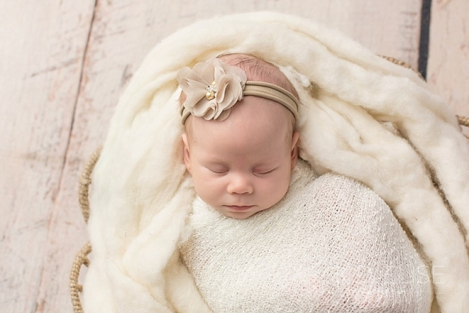 Close up photo of baby girl wrapped in cream, laying in a basket filled with cream fur. Newborn photography by Pueblo photographer K.D. Elise Photography.
