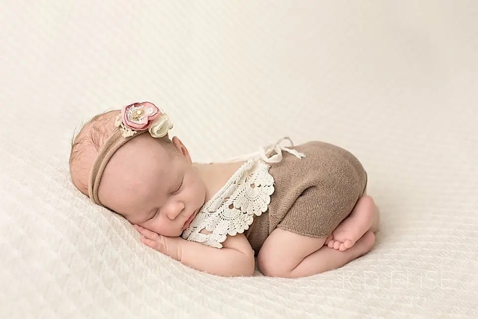 Newborn baby girl in a brown and lace romper with a pink headband. Newborn photo by Pueblo newborn photographer K.D. Elise Photography.