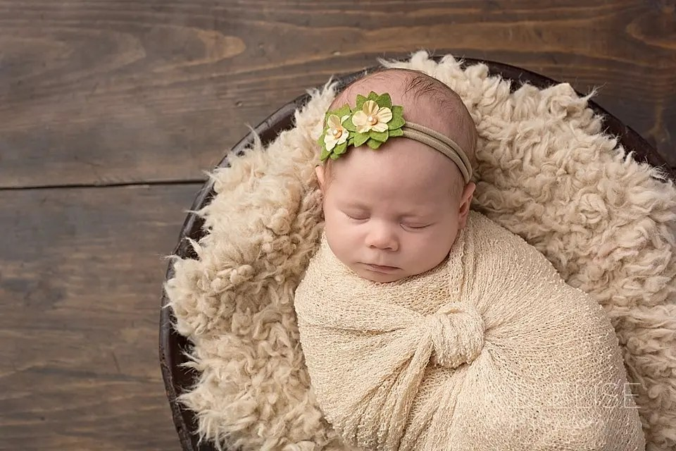 Newborn baby girl wrapped in tan and laying on cream fur. Newborn photography by Pueblo photographer K.D. Elise Photography.