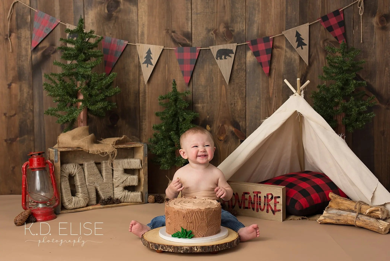 Smiling baby boy during lumberjack themed cake smash session by Pueblo photographer K.D. Elise Photography.
