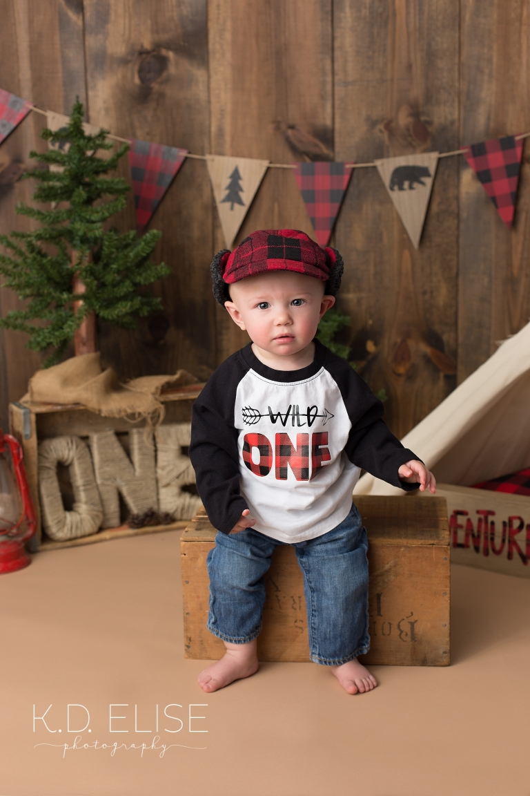 First birthday portrait of baby boy wearing a red plaid hat during first birthday cake smash.