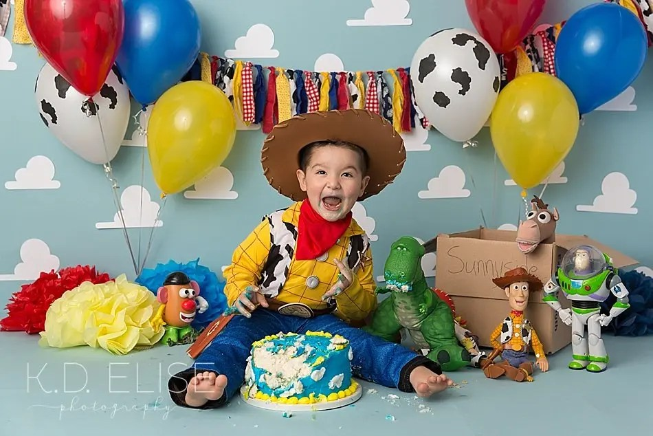 Little boy smiling at the camera during Toy Story themed cake smash with K.D. Elise Photography.