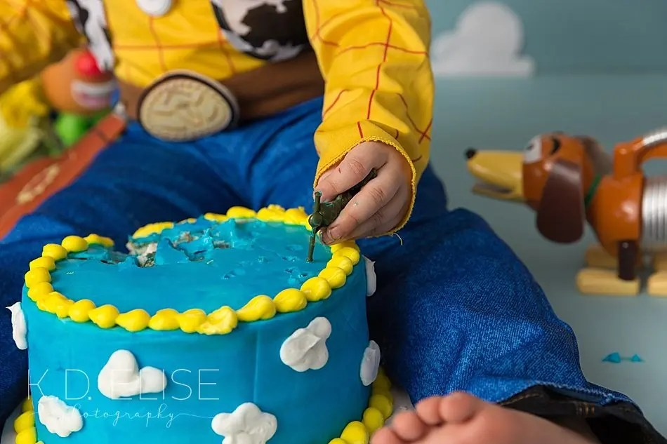 Close up photo of a little boy's hand covered in cake during his Toy Story themed cake smash with Colorado Springs photographer K.D. Elise Photography.