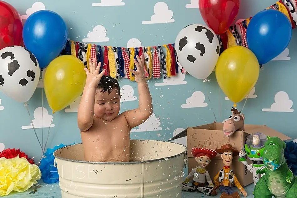 Little boy in a bath after his Toy Story themed cake smash.