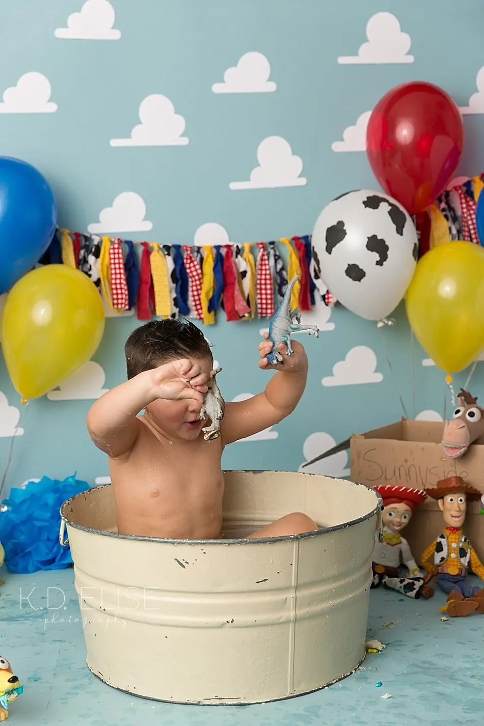 Three year old little boy in a metal wash basin splashing after his Toy Story themed cake smash.