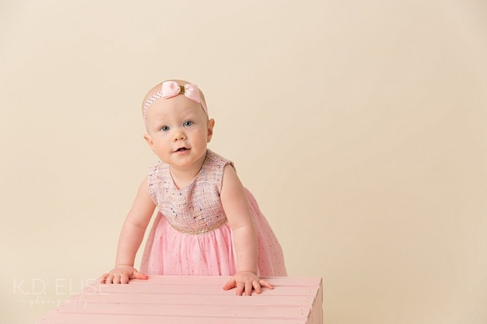 Baby girl in a pink dress standing against a pink crate before her candy themed cake smash with Colorado Springs photographer K.D. Elise Photography.