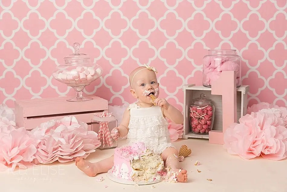 Baby girl taking a bite of cake during candy themed cake smash with K.D. Elise Photography, a photographer in Pueblo, CO.